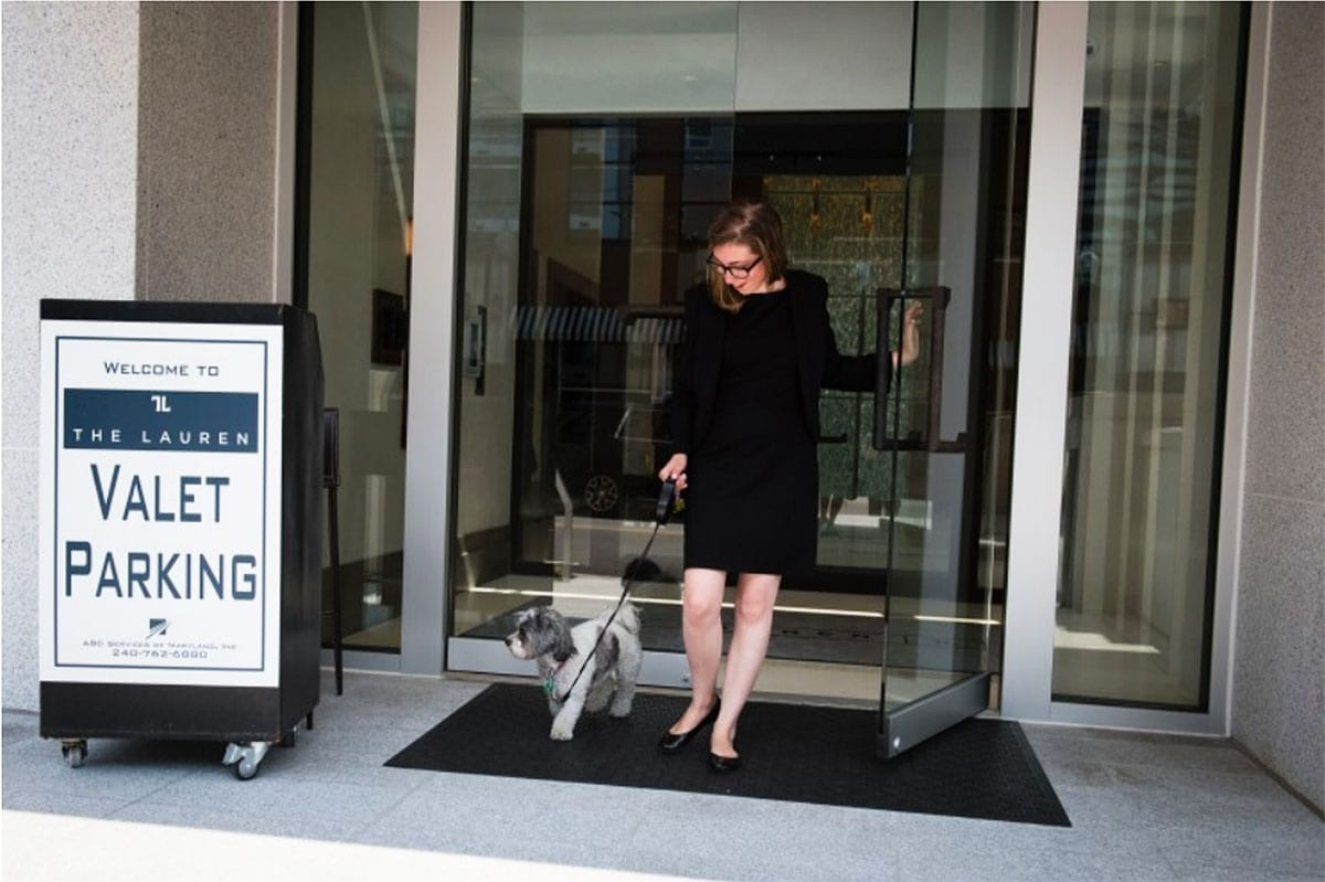 Concierge member Amelia Hess walks a dog for a resident. (Sarah L. Voisin/The Washington Post)